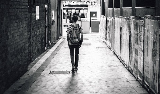 Black and white lonely solo backpacker walking through city street sadly
