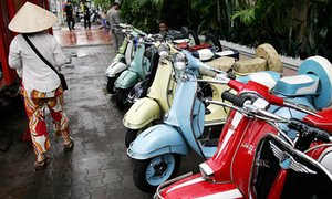 A woman walks past a row of repaired old Vespa scooters displayed for sale along a street in Ho Chi Minh