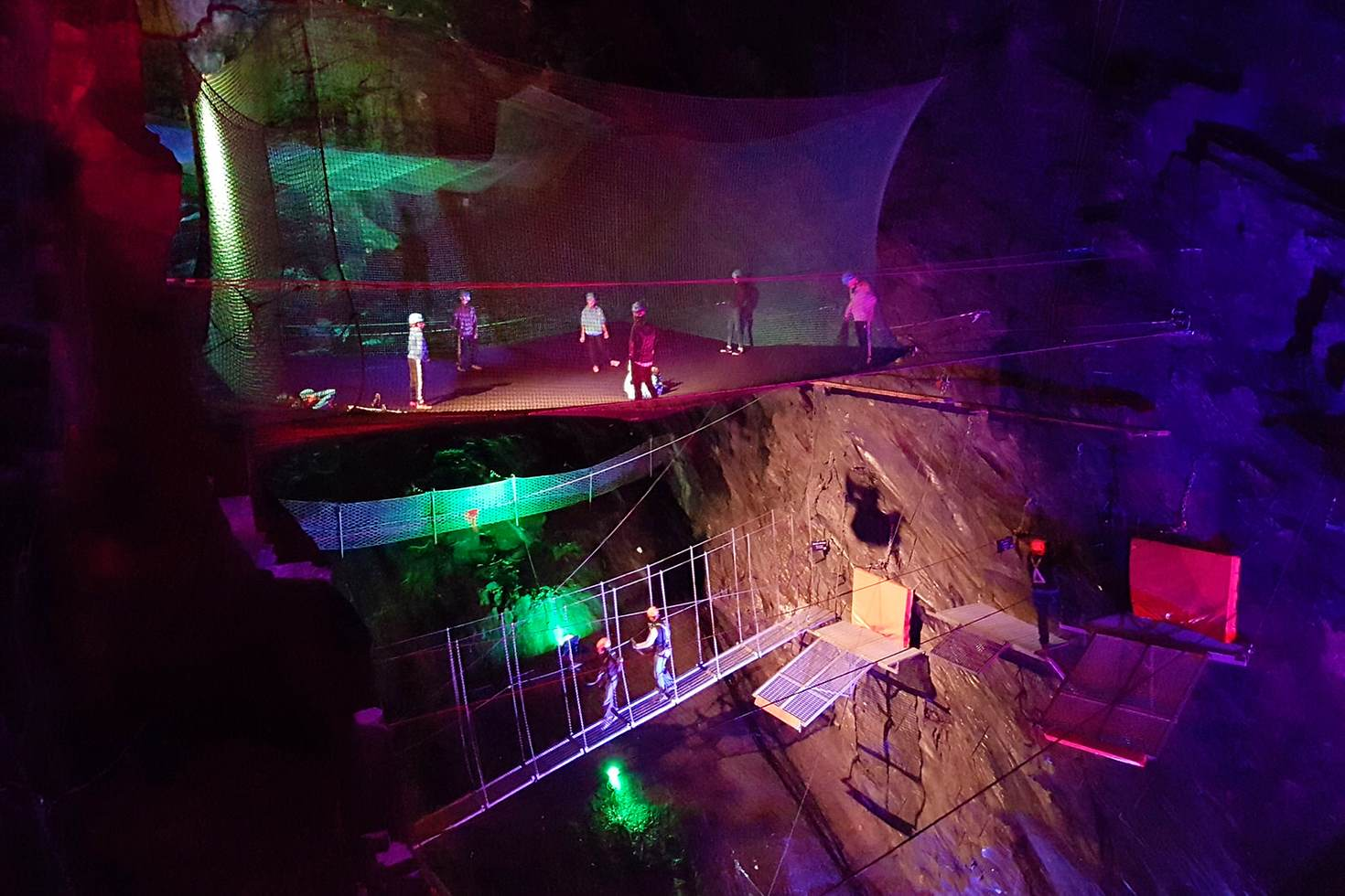 Trampolines and zip lines hang in cathedral-sized caves at Blaenau Ffestiniog © James Smart / Lonely Planet